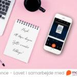 Skrivebord med notesblok og iphone med mofibo, hvor jytte fra marketing bliver afspillet