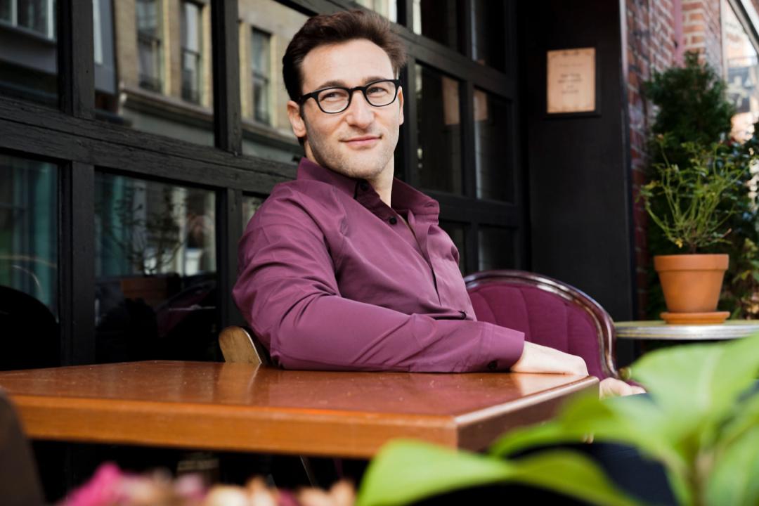 Simon Sinek forfatter til selvudviklingsbogen for selvstændige start med hvorfor. På cafe i lilla skjorte.